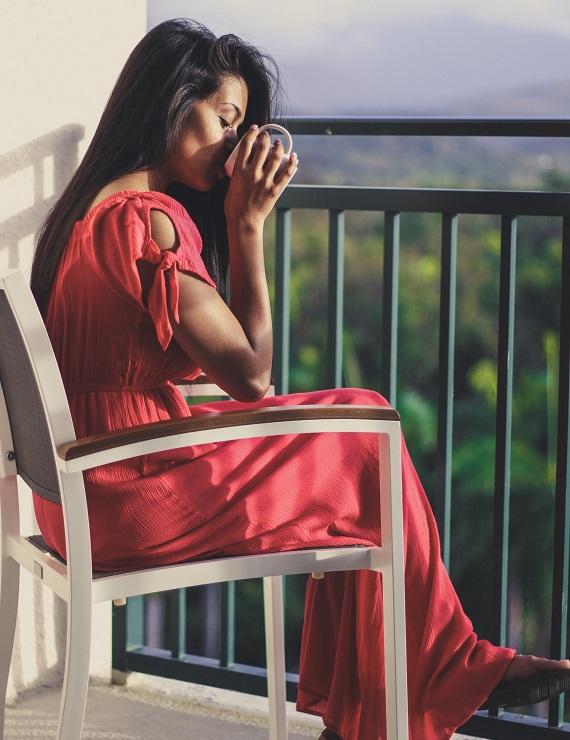 woman in a pink dress drinking detox tea