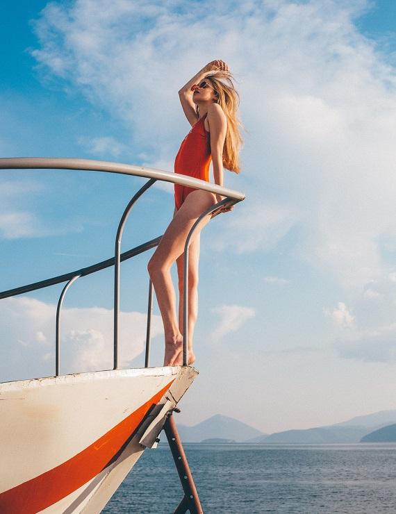 woman on a boat wearing orange swimsuit