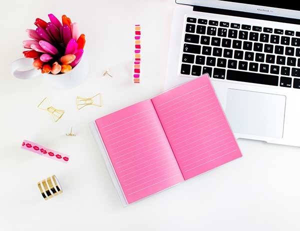 pink notebook with a laptop and colourful pens 600x462